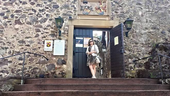 Veronika veste vestido de animal print com blazer branco, sandália cinza claro e bolsa p&b para conhecer a cidade de Idar-Oberstein