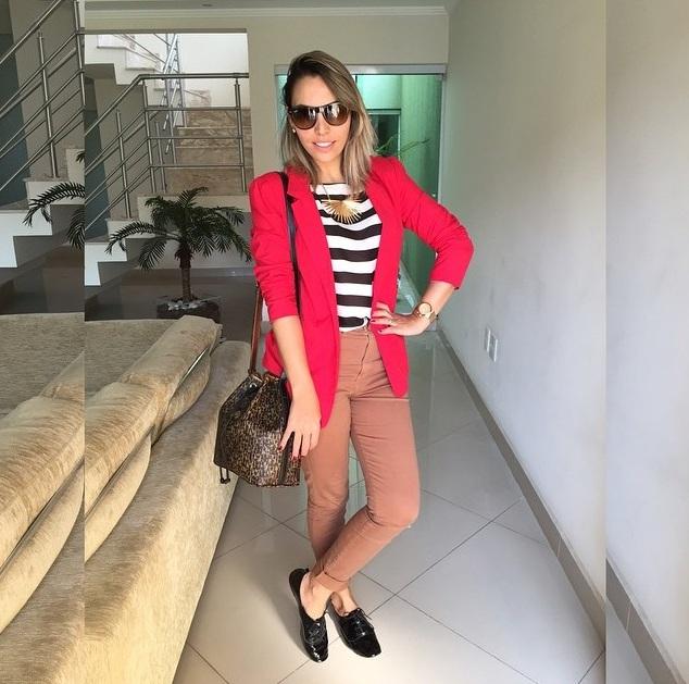 Janaína veste blusa listrada p&b com blazer vermelho por cima. Em baixo, calça caramelo, bolsa marrom tipo saco e sapato preto tipo orford
