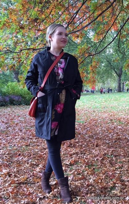 Vestido floral de fundo escuro usado com legging preta e casaco também preto. Nos pés, bota de cano curto marrom e bolsa de ombro laranja.