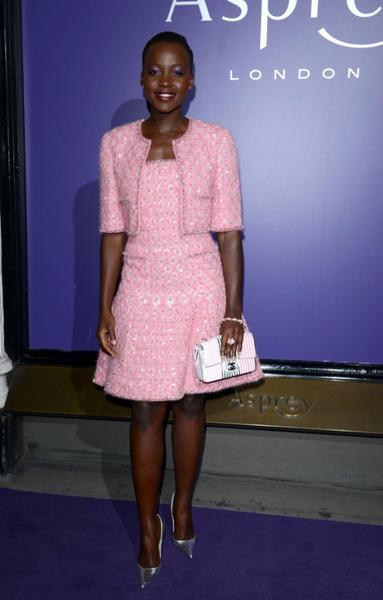 Lupita veste vestido com casaqueto de tweed na cor rosa