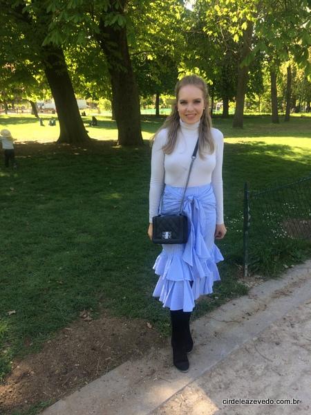Eu usando blusa de gola gelo, saia midi de babados azul e branca, com legging e botas pretas