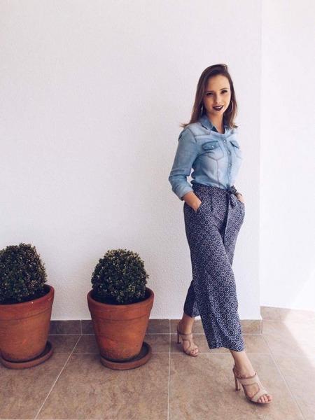Kathlen usa blusa de magas compridas com lavagem jeans, calça pantacourt estampada com detalhe de amarração na cintura e sandália nude