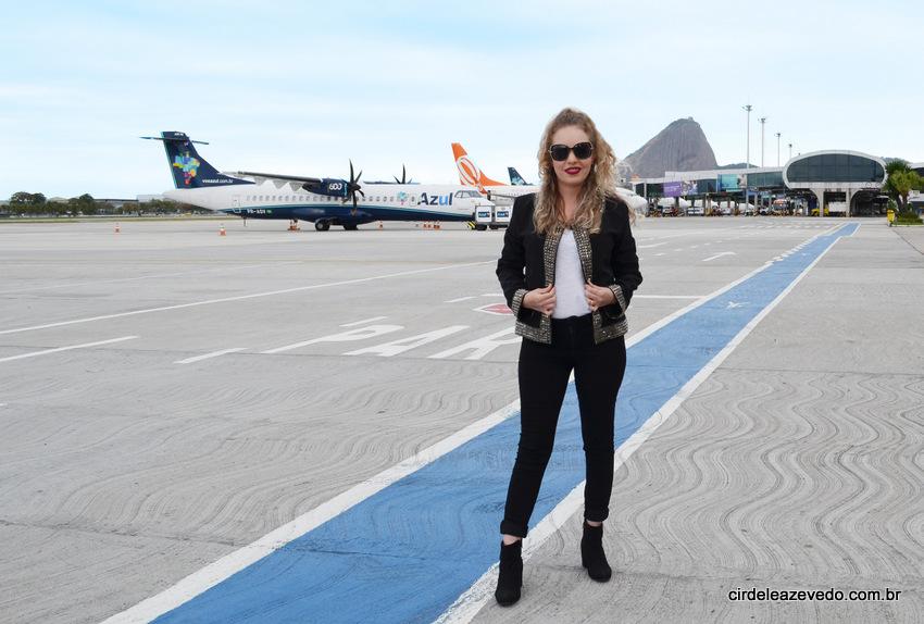 Eu na pista do aeroporto Santos Dumont usando calça, casaco e bota pre, regata branca e óculos de sol