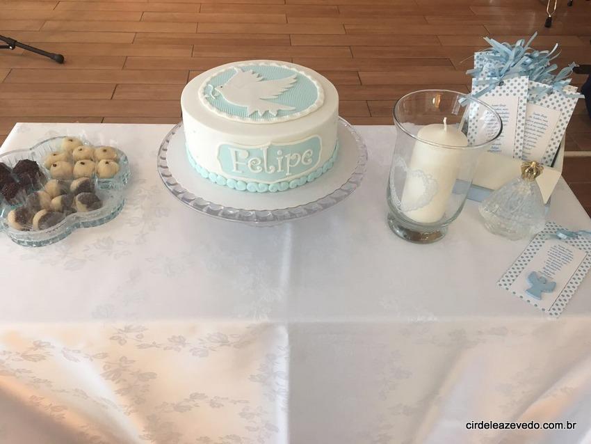 Mesa da comemoração do batizado com docinhos, bolo, vela e lembrancinhas