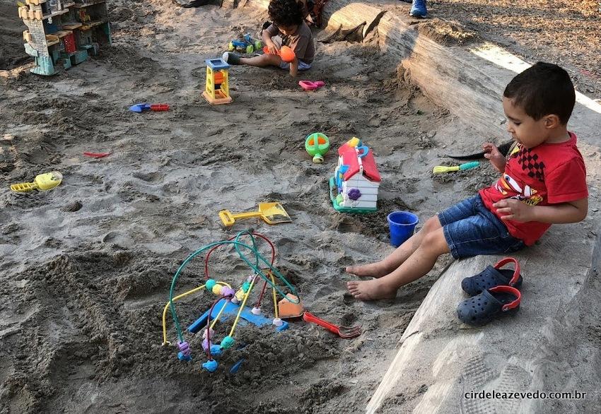 O pequeno curtindo a caixa de areia em um dos parques da cidade