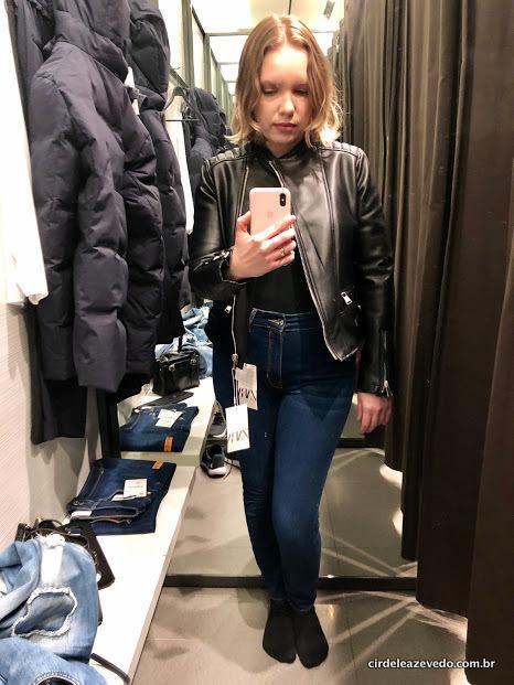 Eu sandy calça jeans azul, blusa e jaqueta de couro falso, ambas na cor preta