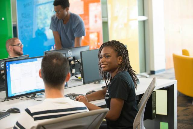 FIU Student smiling in the Software Lab.