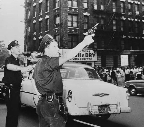 """""""Two policemen pursue the members of a New York street gang after a fight broke out. November 1961.""""(Getty)"""