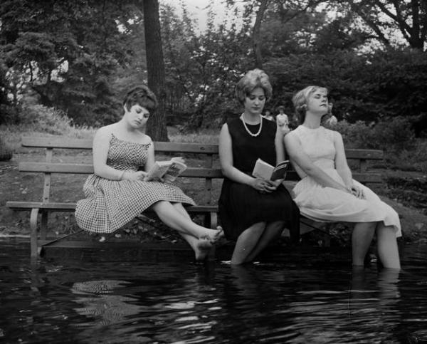 """""""Three women keep cool during a heat wave by moving a park bench into the water in Central Park. September 1961.""""(Getty)"""