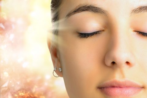 Extreme Close up face shot of young woman with eyes closed.Girl doing mental exercise against bright background with light beam.