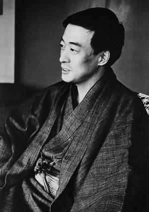 着物を着て、横を向いた姿で上半身を撮った吉行淳之介の白黒写真。