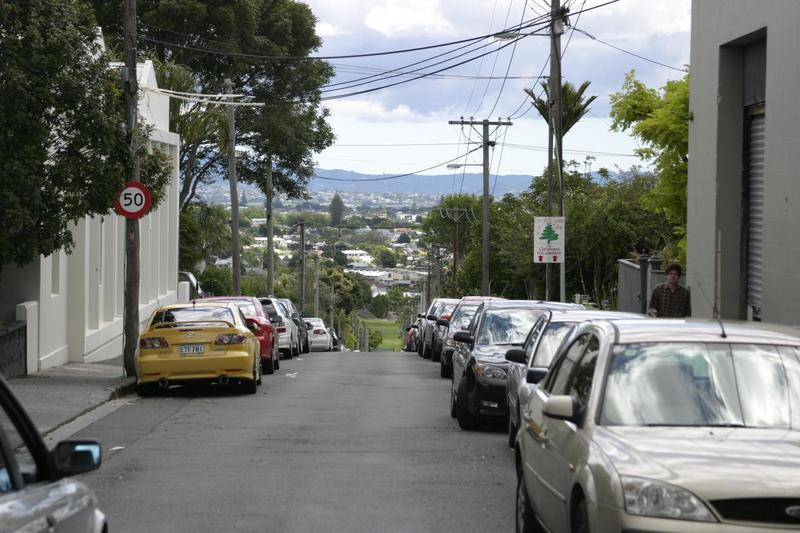 A residential street in Auckland full of parked cars.