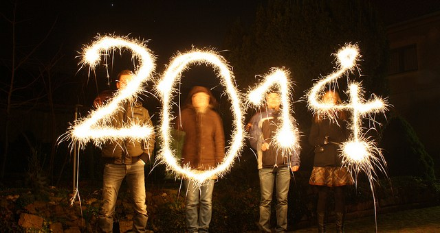 Four people swirling sparklers in front of them so the light patterns spell out 2-0-1-4.