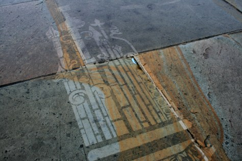 Detail, stencilled drawing jet washed onto the pavement in Queens Gardens, Warrington