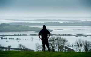 Young Paul O Sullivan of Cooga, Kildysart looking out over the family farm and other neighbour's farms which are under deep flood water from the Shannon Estuary. Photograph by John Kelly.