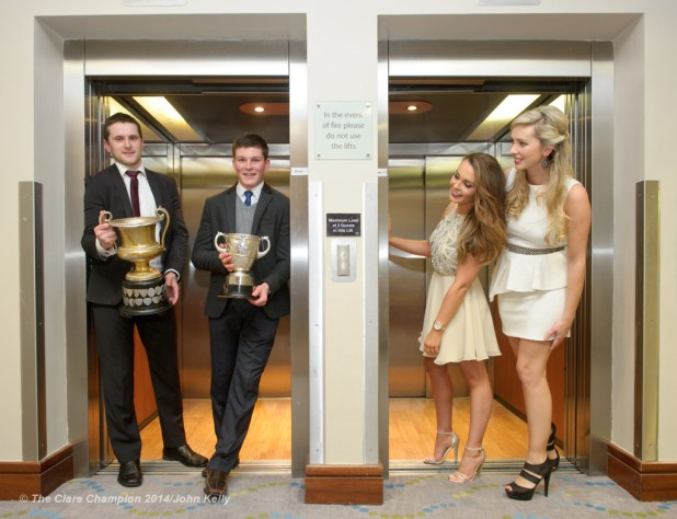 Getting a lift...Football captain Michael Hawes and Hurling captain Liam Markham are watched by their partners Chloe Neylon, and Bernadette Crowe during a photocall at the Cratloe GAA Victory dinner in The Radisson hotel. Photograph by John Kelly.