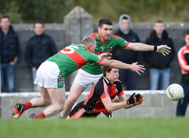 Brian Carrig of Clondegad in action against Thomas O Connor and Darren Hickey of Kilmurry Ibrickane during their Cusack Cup final in Kilmihil.