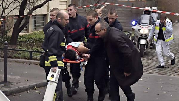 Uno de los heridos es trasladado luego de atentado en la redacción del periódico satírico Charlie Hebdo. (AFP)