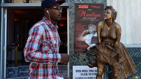 Un peatón pasa junto a una estatua de Marilyn Monroe en el Museo de Hollywood, donde una exposición sobre su vida por el 50 º aniversario de su muerte el 5 de agosto de 1962. (AFP)