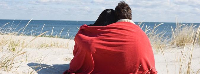 Paar kuschelt sich am Strand in Decke und blickt zum Horizont