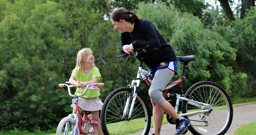mom with prosthetic riding bicycle with daughter