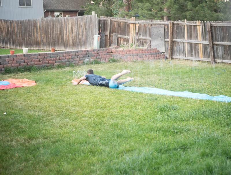 Boy sliding down slip-n-slide
