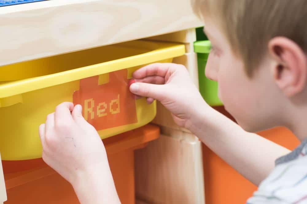 child placing label on box