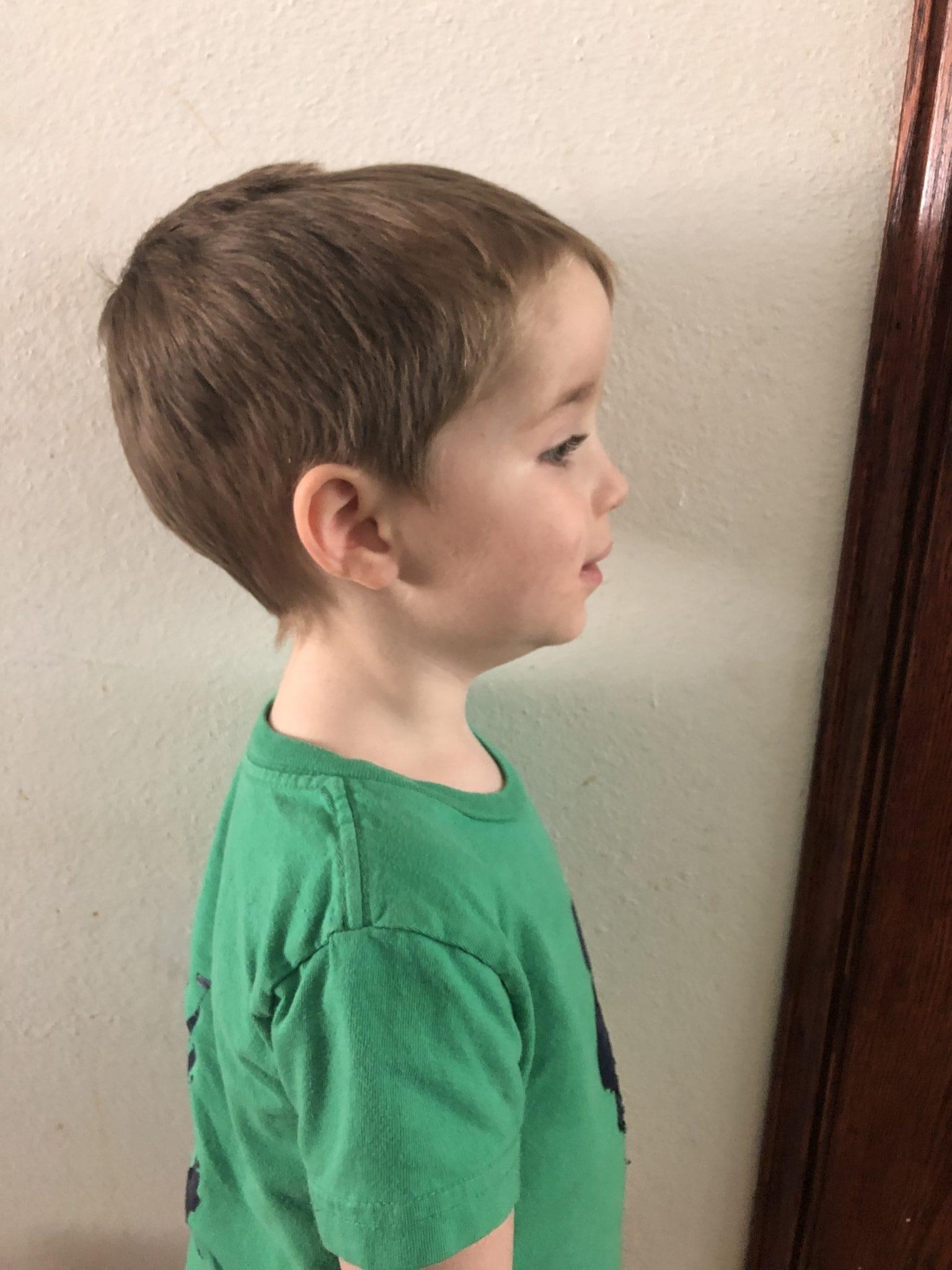 little boy standing by wall