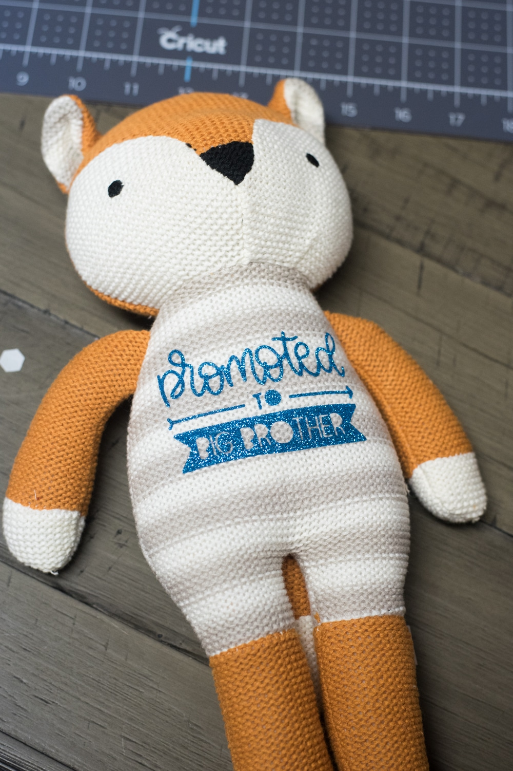 "stuffed knit fox with ""promoted to brother"" on the front"