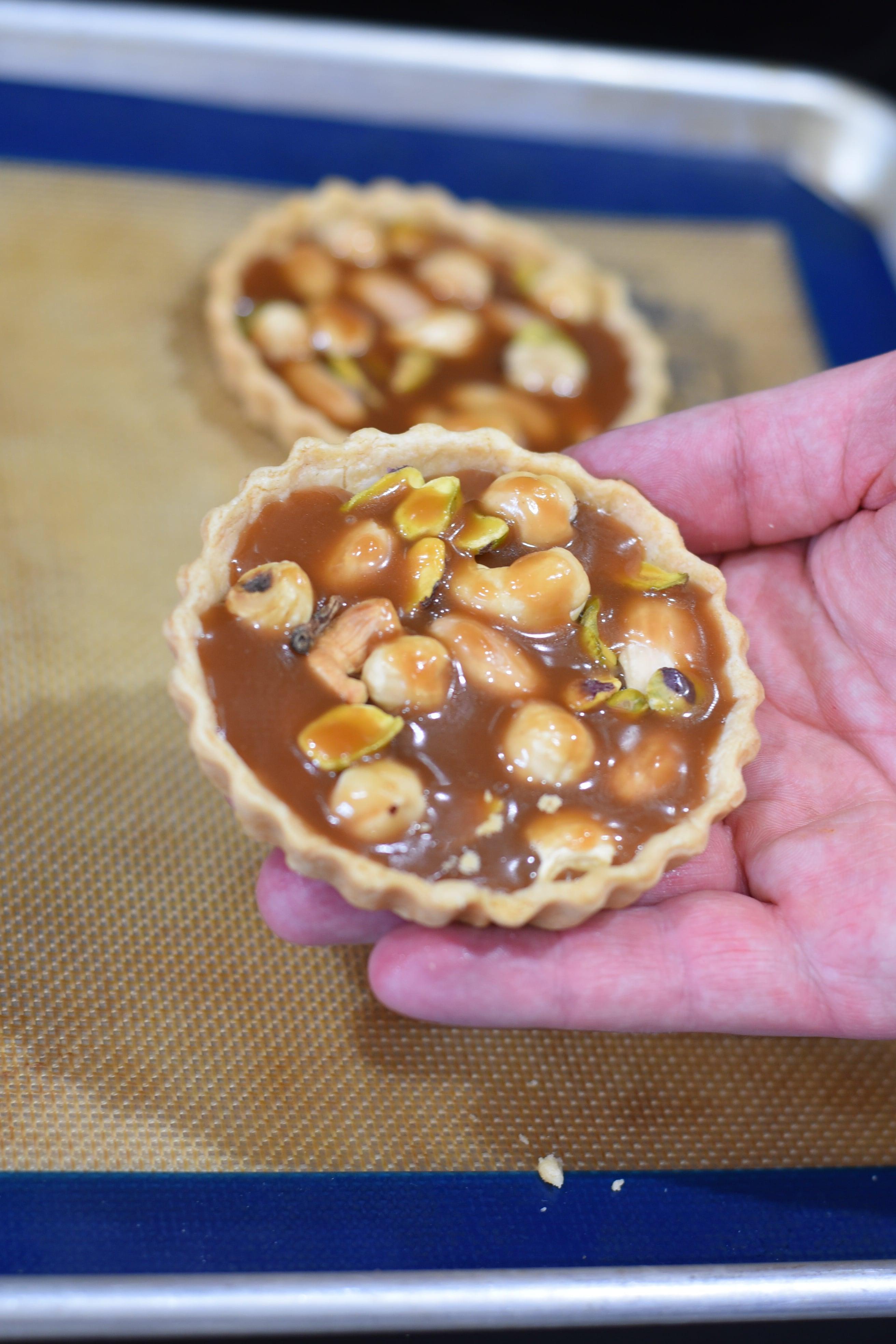 holding a wildgrain caramel tart