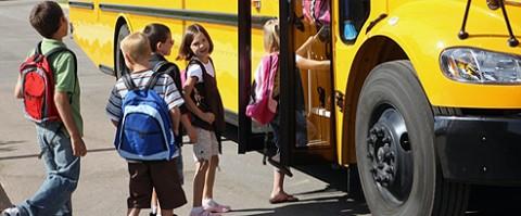 School Kids getting on a bus.