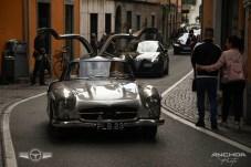 Un Mercedes 300 SL con alas de gaviota desplegadas pasando por una calle de Cernobbio.