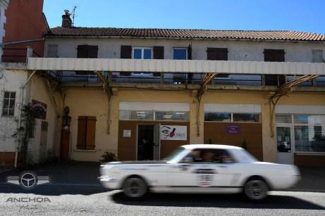 Un Ford Mustang pasando por una antigua gasolinera.