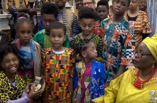 """Founder of Sankofa Children's Museum of African Cultures, Esther """"Mama Kiki"""" Armstrong (in yellow) with children and their parents at her Sankofa African & World Bazaar shop in Baltimore. (Photo: CBS Baltimore)"""