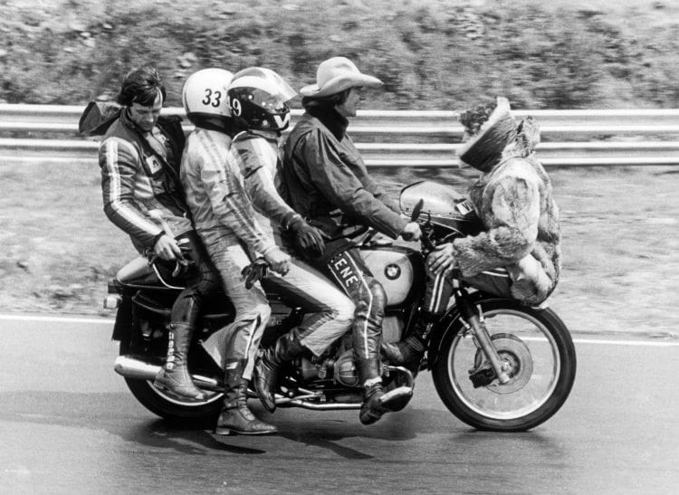 Five men on a motorcycle June 1974, Phil Read perched on the front mudguard, Barry Sheen has hold of the handle bars, behind him Pete Williams then Paul Smart and right at the back is Gianfranco Bonera.