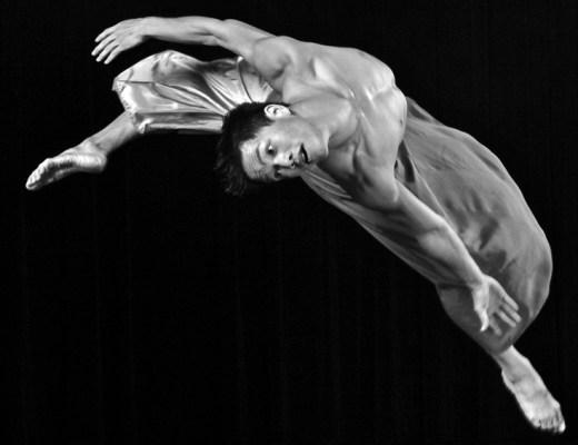 Bailarino caindo em uma pirueta com braços e pernas em movimento formando um arco em um retrato de grande impacto.A foto está em preto e branco e o jogo de sombras contribui para a beleza do conjunto.