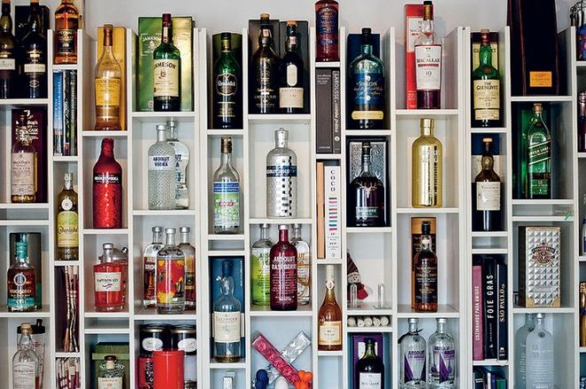 Uma prateleira branca embutida de alto abaixo na parede com vários nichos retangulares onde estão acomodadas garrafas de bebida de vários tamanhos e marcas . Um bar que não ocupa espaço e está visível sempre.
