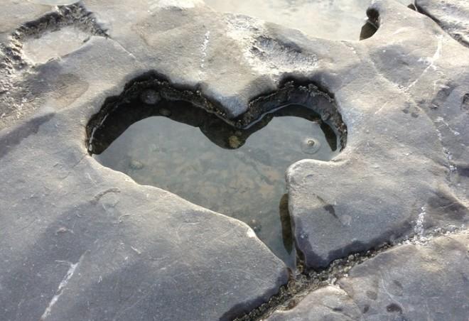 Recorte em uma rocha formando um coração cheio de água