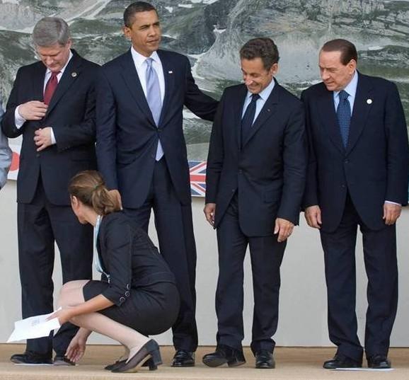 Presidente Barack Obama ao lado do Presidente Sarkozi da França e do Primeiro Ministro Berlusconi da Itália e todos olham para uma cerimonialista retirando os papeis de marcação deles no palco
