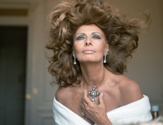 retrato da atriz italiana, Sofia Loren, já com mais de 60 anos. Ela está com os belos ombros a mostra usando um vestido tomara que caia branco e os cabelos abundantes ao vento. Seu rosto continua belíssimo, com poucos sinais da idade e os imensos olhos verdes, marca registrada brilham mais do que os brincos e o grande pendente de brilhantes que enfeitam o pescoço da diva..