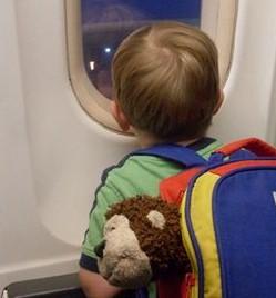 Menino de 3 anos dentro de um avião olhando pela janela. Está com uma mochila colorida nas costas de onde aparece a cabeça de um leão de pelúcia