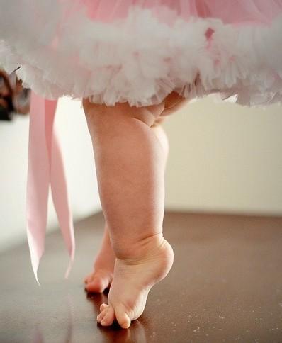 A foto mostra apenas as pernas rechonchudas de uma bebê de 1 ano de idade, usando um vestidinho de festa de tule rosa e branco, descalça sobre o piso de madeira da sala, na ponta dos pezinhos gordos como se estivesse fazendo força para se equilibrar