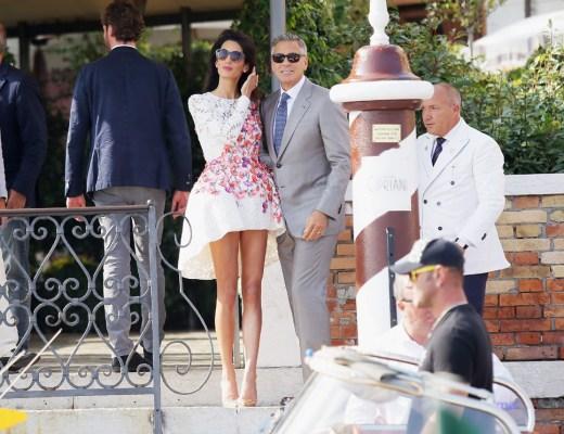 Ator George Clooney, de cabelos grisalhos e oculos escuros, vestido um lindo terno cinza claro , camisa branca e gravata cinza escuro, abraça lateralmente sua noiva , , colocando sua mão nas costas da noiva, que usa óculos escuros também , usa vestido claro com desenhos de varios tons de flores, longos cabelos pretos - ambos estão no deck para embarcar no barco.
