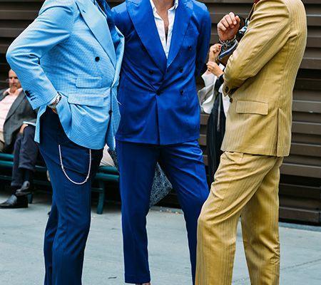 3 homens italianos estão em pé numa praça de Roma, um deles está com blaizer azul claro e calça azul escura , sem meia e sapatos colorido azul e amarelo, o outro com um terno azul petroleo e camisa branca e o outro com terno cor camelo, sapato marrom escuro sem meia.