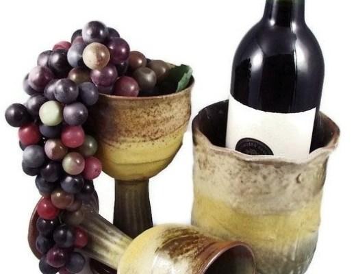 cooler de cerâmica com uma garrafa de vinho dentro, ao lado de duas taças também em cerâmica. uma está em pé com uvas dentro e a outra está caída.