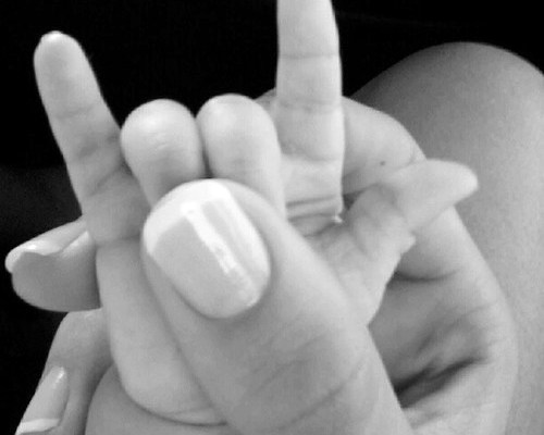 mão de mulher com unhas bem tratadas segurando a mão de um bebê recém nascido e com o dedão ela segura os dedilho anular e médio da criança formando o símbolo de heavy metal