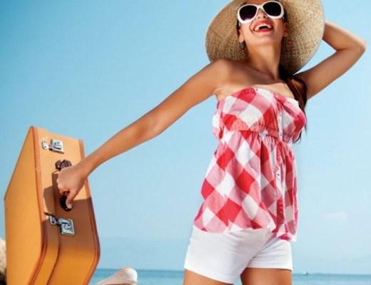 Jovem mulher vestida de shorts brancos e blusa tomara que caia xadrez em vermelho e branco. Está com um grande chapéu de palha e óculos escuros, segurando uma mala. Ao fundo, uma mar lindo, quase se juntando com o céu