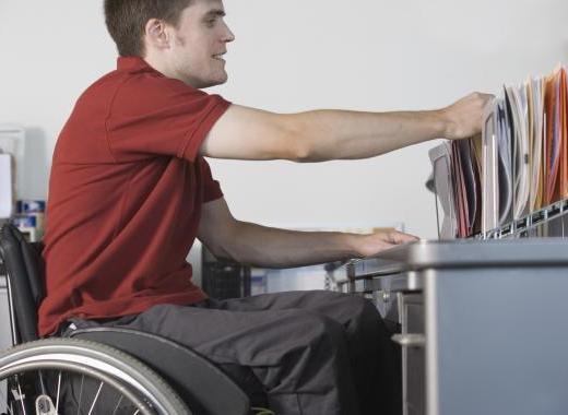 rapaz jovem, sentado em uma cadeira de rodas, mexe em algumas pastas de um arquivo