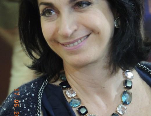 Claudia Matarazzo, seus rosto está inclinado para a direita, sorri, um olhar para o seu interlocutor, usa um lindo brinco colorido e prata junto a orelha, um belíssimo colar de pedra grandes, em varios tons de verde e azul. sua blusa presta de alça, estilo camiseta, por cima veste um lindo casaco com azul escuro com pequenos detalhes azul claro.