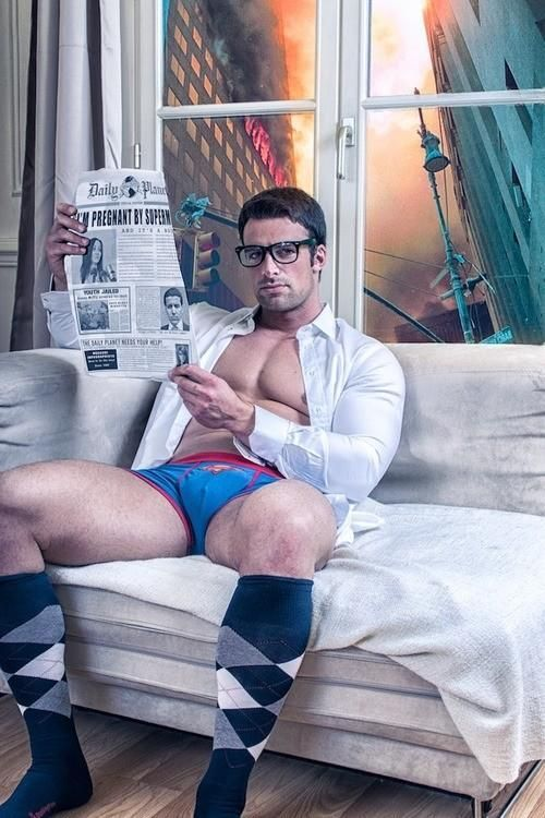 homem jovem, musculoso, sentado num sofá , rente a uma janela de vidro, ele lê uma pagina de jornal, usando apenas uma cueca azul, camisa social branca, e meias de cores quadriculadas.